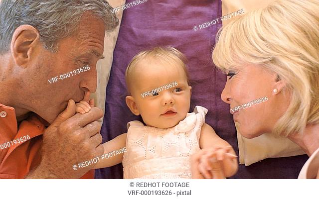 Overhead shot of grandparents and baby granddaughter playing on cushions on floor