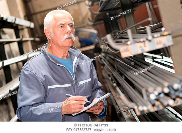 senior worker counting metal bars in warehouse