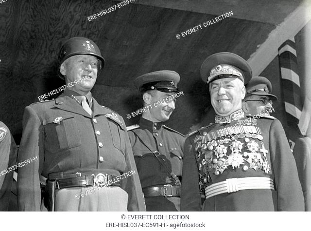 General George S. Patton (left) and Soviet Marshall Gregory Zhukov review troops in Berlin. Soldiers of four nations marched in a parade to celebrate the Allied...
