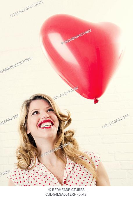Smiling woman with heart shaped balloon