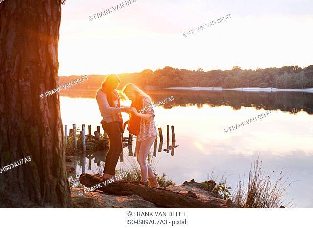Friends enjoying lake at sunset