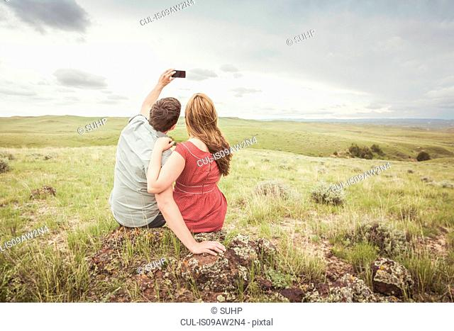 Rear view of young couple sitting on hilltop taking smartphone selfie, Cody, Wyoming, USA