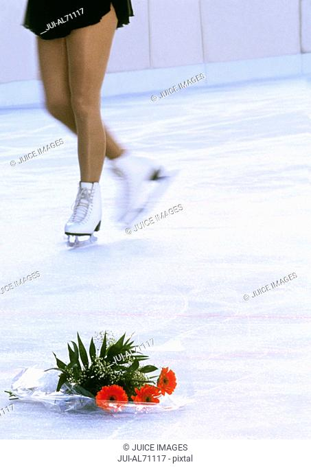 Blurred view of a woman skating with white ice skates with a bouquet of flowers on the ice