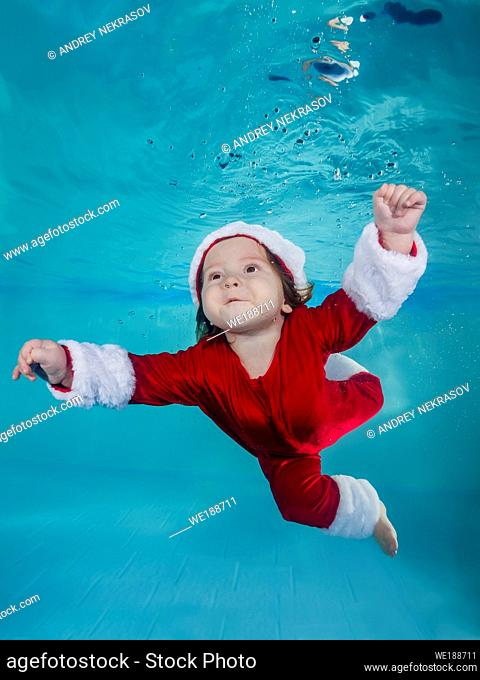 Funny long-haired boy in a Christmas outfit dives underwater in a swimming pool