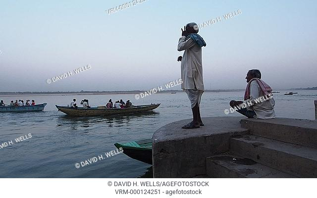 View of boats on river, men talking in the foreground in Varanasi, Uttar Pradesh, India