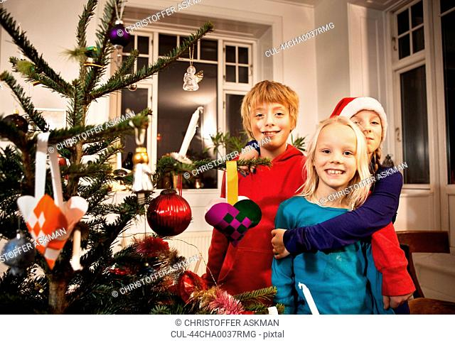 Children smiling with Christmas tree