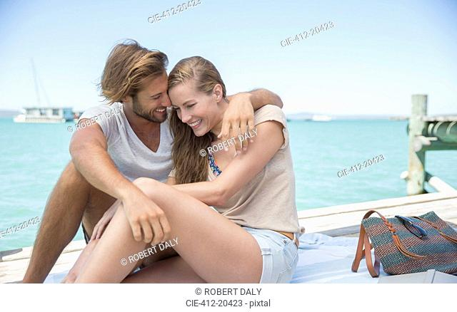 Couple sitting together on edge of wooden dock