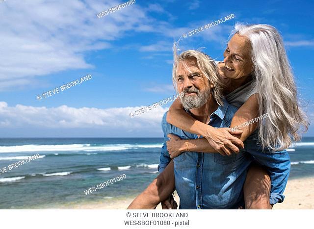 Handsome senior couple having fun at the beach