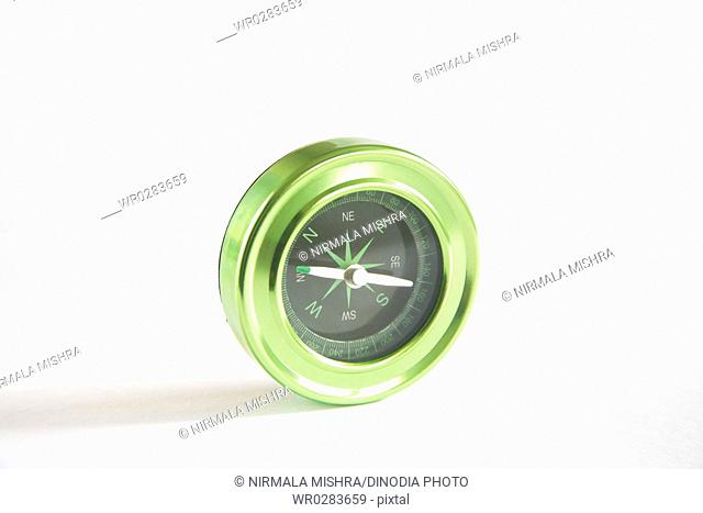 Compass instrument with magnetic needle indicating east north south west on white background