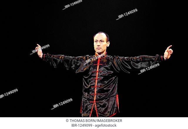 Kung Fu fighter with outstretched arms wearing a black, Chinese Kung Fu suit, Chinese New Year festival of the Kung Fu Academy in the auditorium of the...