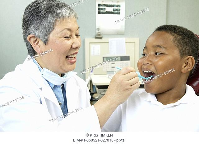 Senior Asian female dentist examining young male patient