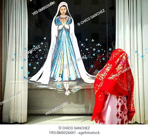 A Mexican woman dressed with traditional clothing watches a painting of Our Lady of Rosary in Fatima, Portugal