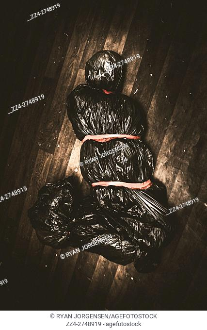 Torture victim tied and bound in black bag lying on the floor. Grounds of crime and misconduct