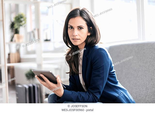 Portrait of businesswoman with tablet on couch