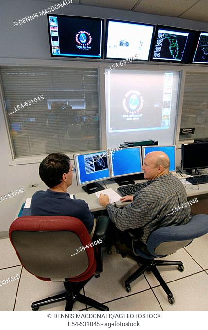 Meteorologists Confer Using Technology  in Work Area in National Oceanic and Atmospheric Administration (NOAA). National Weather Service Station