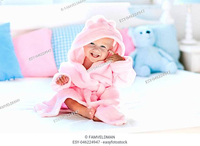 Cute happy laughing baby in soft bathrobe after bath playing on white bed with blue and pink pillows in sunny kids room. Child in clean and dry towel