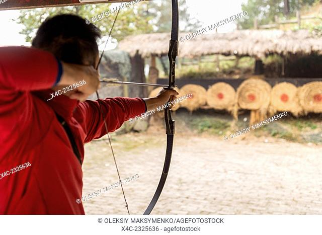 Person shooting arrows from a bow, practicing archery in Zhanhjiajie, China