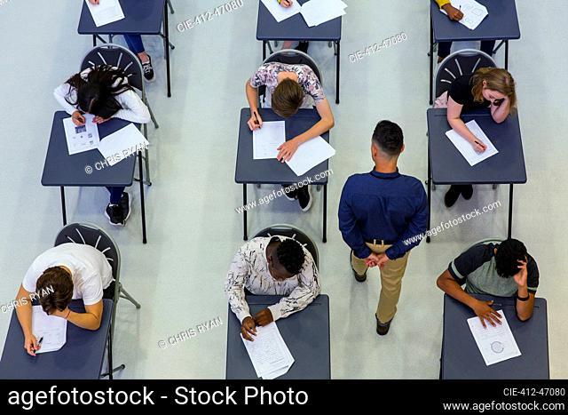 High school teacher supervising students taking exam at desks