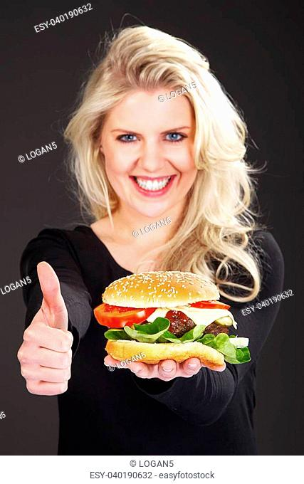 pretty woman with hamburger laughs and holds thumbs up