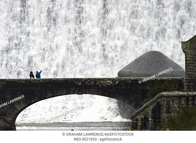 A couple look at the water surging over the Caban Coch Dam in the Elan Valley, in Powys, Wales, UK