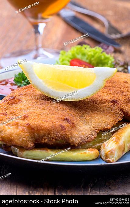 wiener schnitzel with fries on a plate