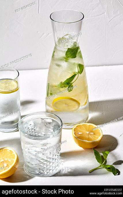 glasses with lemon water and peppermint on table