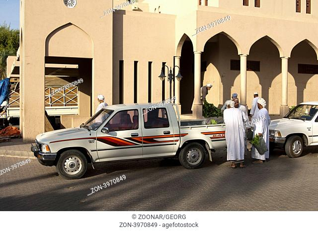 Arabische Männer diskutieren an einem Pickup, Strassenszene in Nizwa, Sultanat Oman / Arab men debating at a pick-up truck, street scene in Nizwa