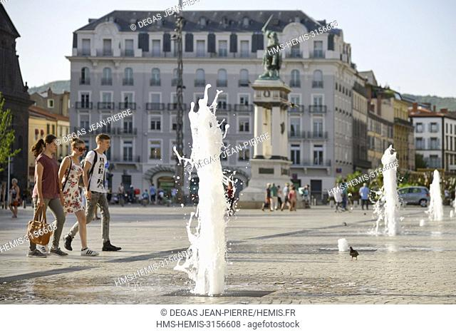 France, Puy de Dome, Clermont Ferrand, roup of young people walking on an esplanade to the mileu of water jets