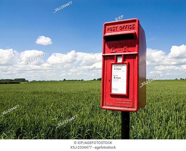 Rural red post box beside a crop field in summer, England, UK