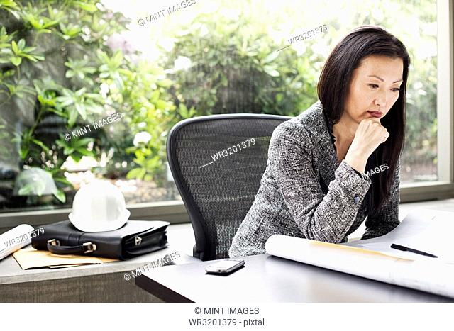 An Asian businesswoman working on architectural plans in her business office