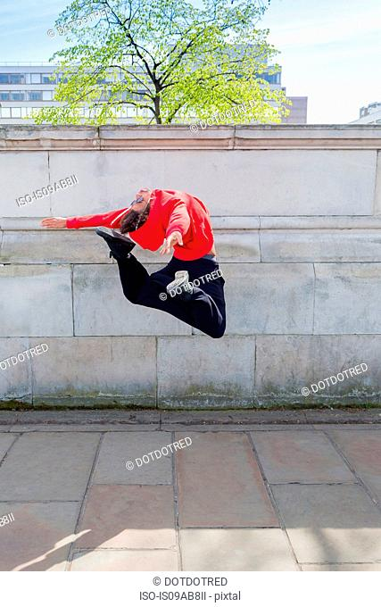 Young male dancer mid air in city