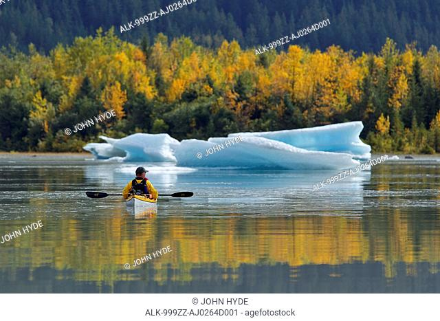Sea kayaker views an iceberg on the calm water of Mendenhall Lake near Juneau, Southeast Alaska, Autumn