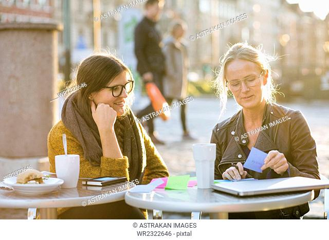 Businesswoman writing notes with colleague on table at sidewalk cafe