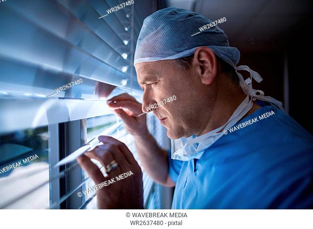 Surgeon looking through window blind at hospital