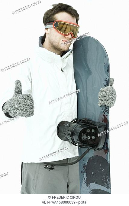 Young male snowboarder, giving thumbs up sign to camera
