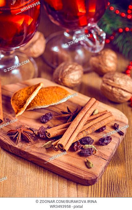 Spices - cinnamon sticks, star anise, cloves and allspice - typical for Christmas baking and decoration and Two glasses of mulled wine