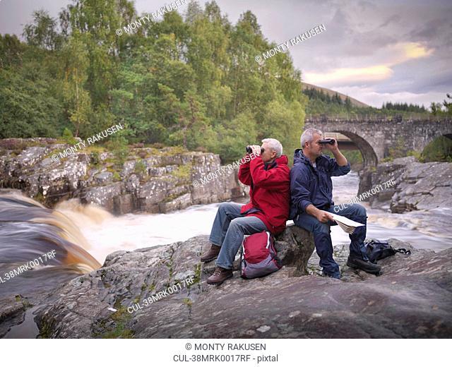 Hikers using binoculars by rocky river
