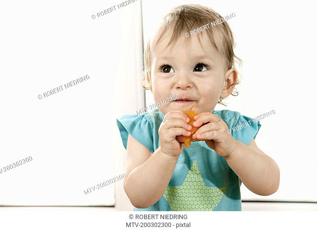 Baby girl eating fruit portrait happy smiling