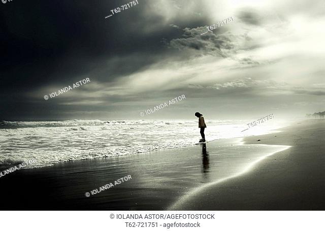 Joven paseando solo por la orilla del mar en invierno