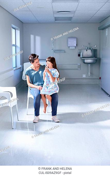 Girl patient sitting on her mothers lap in hospital children's ward