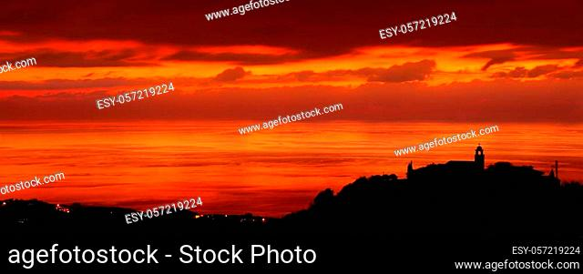 Silhouette of a little coastal town, church on the hill on sunset light, amazing panoramic view, stunning cityscape