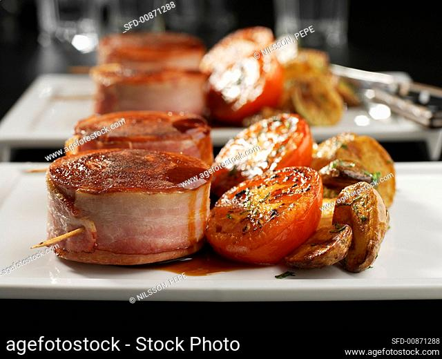 Slice of sausage wrapped in bacon, tomatoes and potatoes