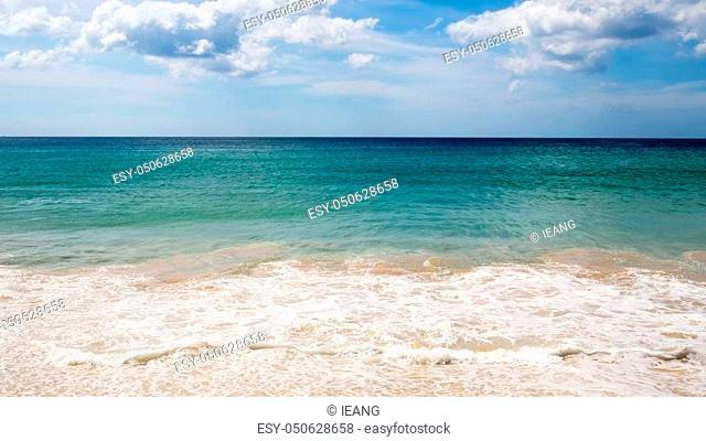 Wave, sea, sky and cloud in summer. Turquoise sea wave foam on Karon beach, Phuket, Thailand. Beautiful sea wave, blue water and nice cloud