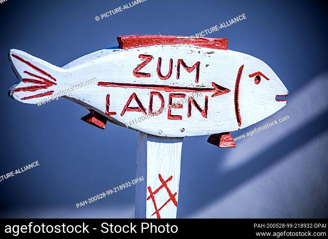 25 May 2020, Mecklenburg-Western Pomerania, Vitte: A wooden signpost in fish form in the harbour on the Baltic Sea island of Hiddensee