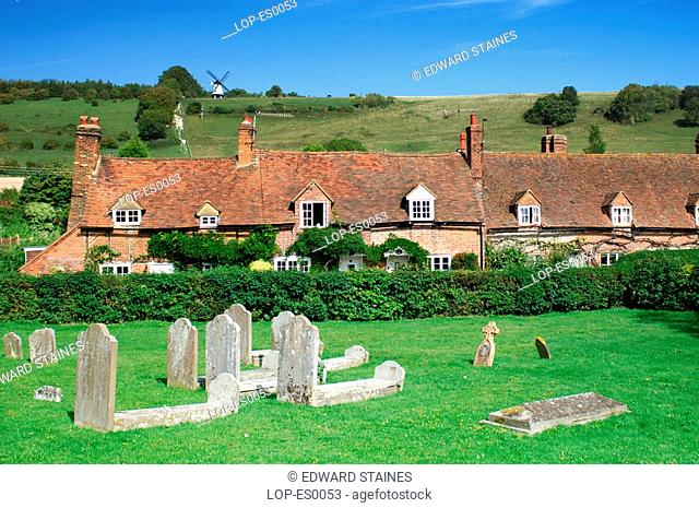 England, Buckinghamshire, Turville, View across graveyard and cottages to the windmill at Turville. Turville is Anglo Saxon meaning 'dry field'