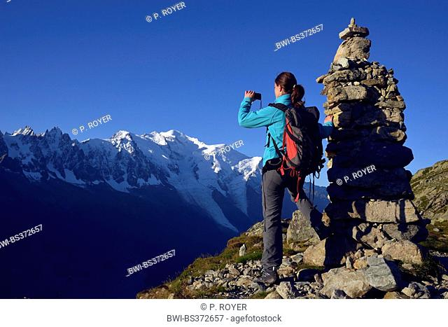 female mountain hiker taking a picture next ot a pile of stones in front of Mont Blanc, the highest summit of Europa, France, Haute-Savoie