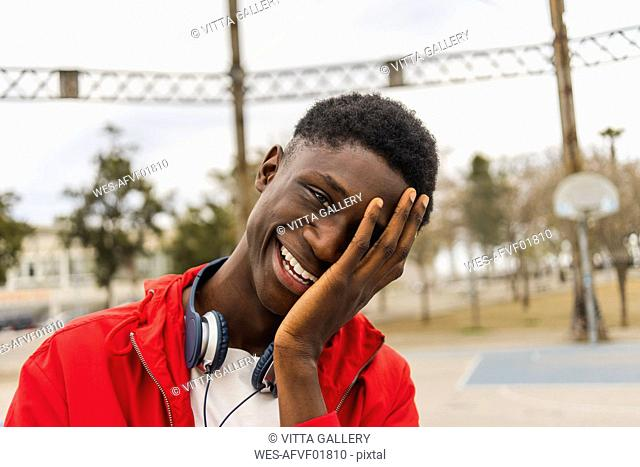 Portrait of a young black man, laughing with hand on his face