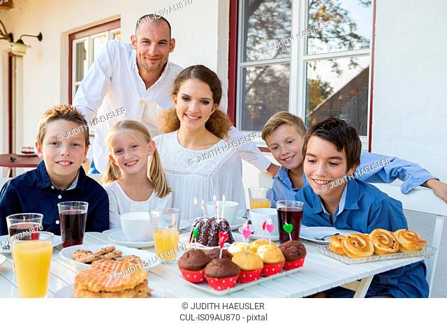 Portrait of mid adult man and family with birthday cake at patio table
