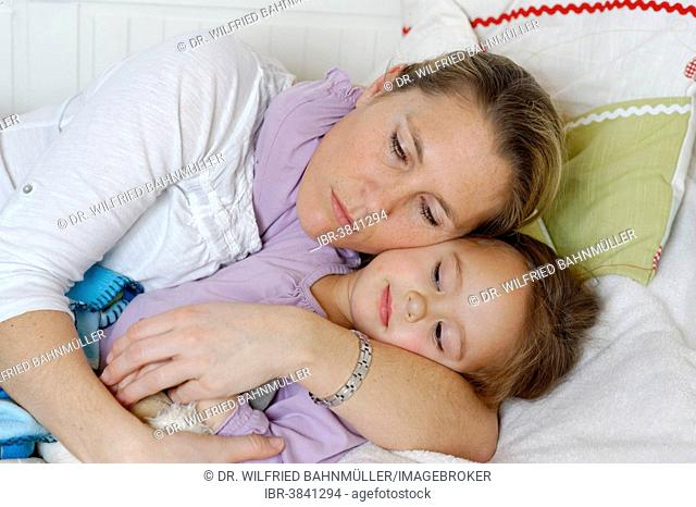 Mother and daughter cuddling in bed, hugging