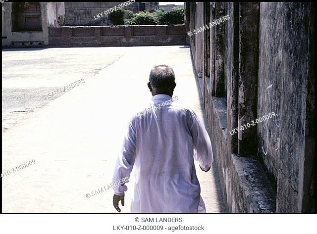 Rear view of Pakistani man walking through outdoor courtyard